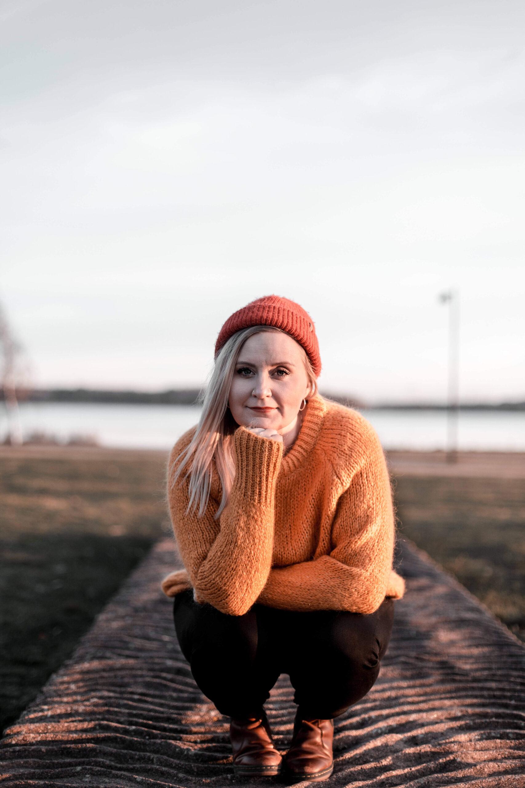 Nainen kyykyssä rannalla punainen pipo päässä ja vaaleat hiukset auki katse kameraan