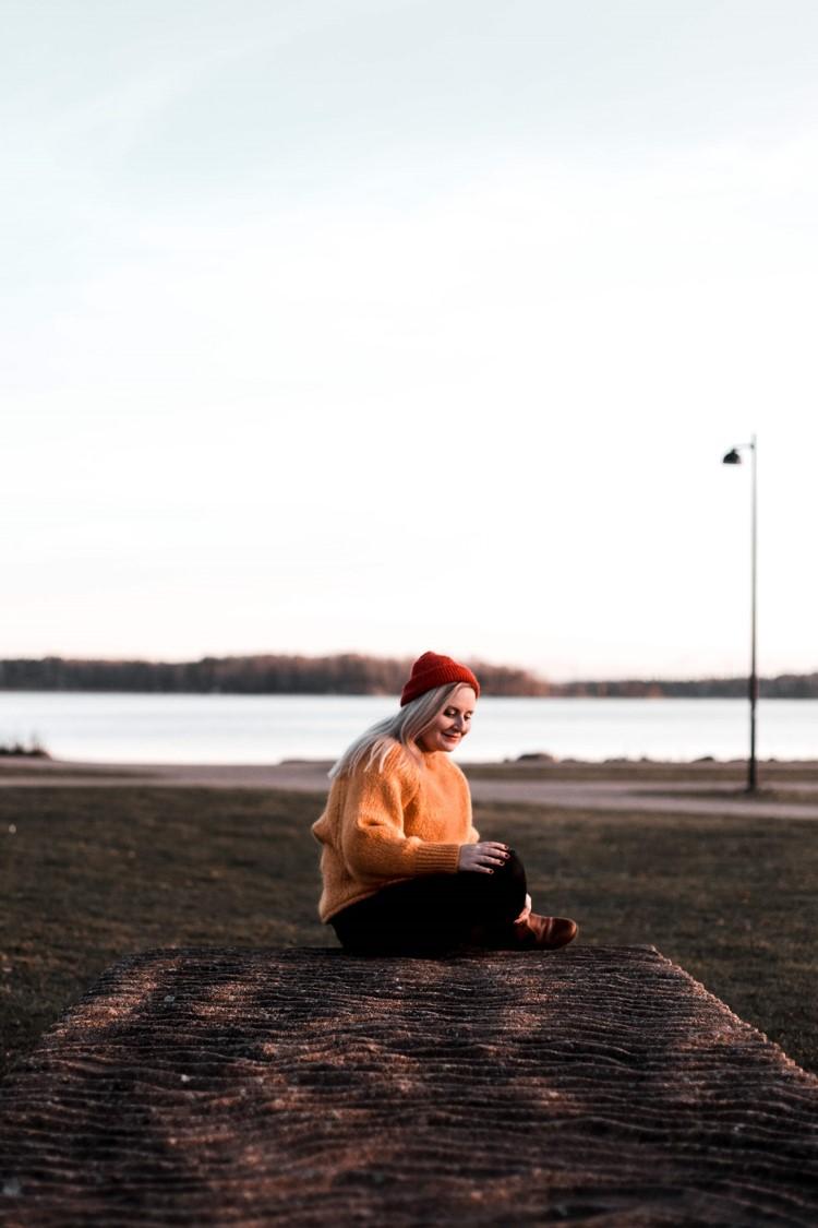 nainen istuu laiturilla oranssi paita päällä ja punainen pipo päässä